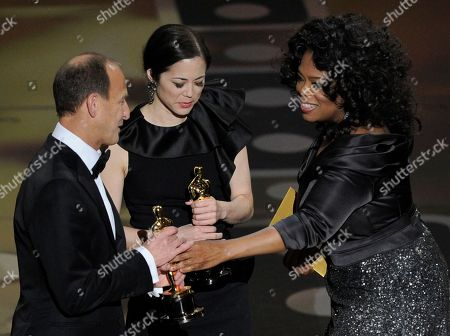 """Oprah Winfrey hand Charles Ferguson and Audrey Marrs their Oscars for best documentary feature for """"Inside Job"""" at the 83rd Academy Awards, in the Hollywood section of Los Angeles"""