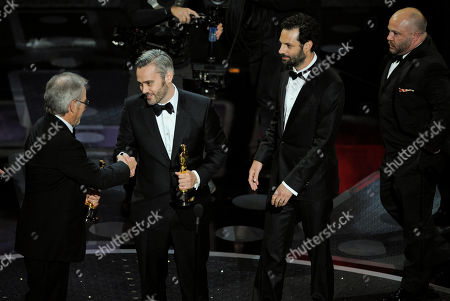 """Steven Spielberg, left to right, gives Iain Canning, Emile Sherman and Gareth Unwin their Oscars for best motion picture for """"The King's Speech"""" at the 83rd Academy Awards, in the Hollywood section of Los Angeles"""