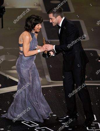 """Jake Gyllenhaal hand Karen Goodman her Oscar for best documentary short subject for """"Strangers No More"""" at the 83rd Academy Awards, in the Hollywood section of Los Angeles"""
