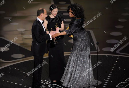 """Oprah Winfrey, Charles Ferguson, Audrey Marrs Oprah Winfrey, right, presents Charles Ferguson, left, and Audrey Marrs, center, with the Oscar for best documentary feature for """"Inside Job"""" at the 83rd Academy Awards, in the Hollywood section of Los Angeles"""