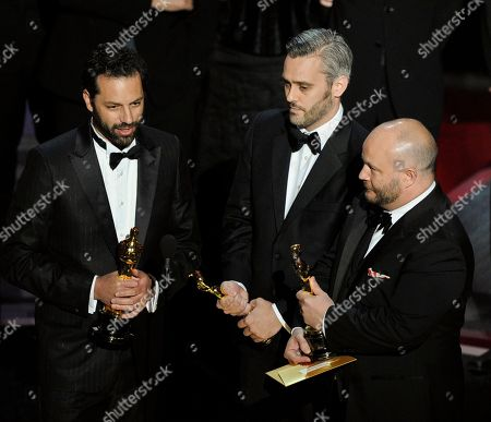 """Iain Canning is flanked by Emile Sherman, left, and Gareth Unwin as they accept the Oscar for best motion picture for """"The King's Speech"""" at the 83rd Academy Awards, in the Hollywood section of Los Angeles"""