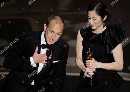 "Charles Ferguson and Audrey Marrs accept the Oscar for best documentary feature for ""Inside Job"" at the 83rd Academy Awards, in the Hollywood section of Los Angeles"