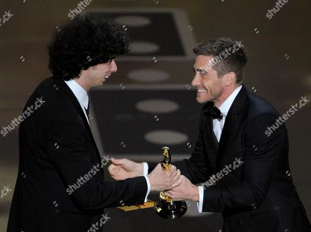 "Jake Gyllenhaal hands Luke Matheny his Oscar for best live action short film for ""God of Love"" at the 83rd Academy Awards, in the Hollywood section of Los Angeles"