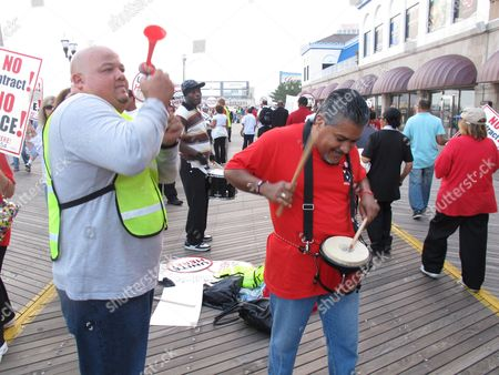In this Sept. 30, 2011 photo, Felix Perez, left, a union representative with Local 54 of Unite-HERE, blows an air horn while Javier Soto, the union's vice president, plays a drum during a union rally in the midst of contract talks in Atlantic City, N.J. The union reached agreement on a new contract, with four casinos owned by Caesars Entertainment Inc.: Caesars, Bally's, Harrah's and the Showboat