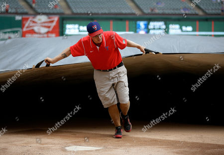 Texas Rangers ground crews employee Stephen Lord approaches home plate as he helps pull the tarp over the field after the Rangers took batting practice before a baseball game against the Milwaukee Brewers, in Arlington, Texas