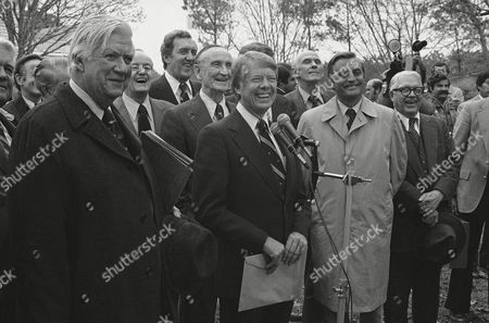 President-elect Jimmy Carter smiles as he talks in Lovejoy, Ga., about his meeting with officials, at the farm of Sen. Herman Talmadge (D-Ga.). From left are House Majority Leader Thomas P. O'Neill of Mass.; Sen. Hubert Humphrey (D-Minn.), Senate Budget Committee Chairman Edmund Muskie (D-Maine); Senate Majority Leader Mike Mansfield of Montana; Carter; Sen. Alan Cranston (D-Calif.); and Vice President-elect Walter Mondale