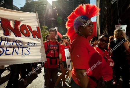 Michelle Harris Michelle Harris, a teacher from Kohn School, sports a colourful wig as she marches with thousands of public school teachers for the second consecutive day on in downtown Chicago. Teachers walked off the job Monday for the first time in 25 years over issues that include pay raises, classroom conditions, job security and teacher evaluations