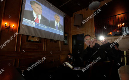 Dan Savage Author and columnist Dan Savage takes a photo with a mobile phone as he sends tweets from a broadcast of the debate between President Barack Obama and Republican challenger Mitt Romney, at the Havana Social Club in Seattle