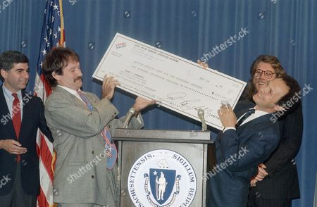 Comedians Billy Crystal, right, and Robin Williams, center, in association with a project called Comic Relief, present a check for the homeless to Governor Michael S. Dukakis, at the State House in Boston. The check is the third in a series totaling over $200,000, given to Boston?s Health Care for the Homeless project. Comic Relief President Bob Zmuda, rear, helps with the presentation