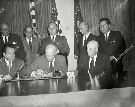 President Dwight D. Eisenhower in a White House ceremony signs a proclamation making Hawaii the 50th state of the union, in Washington. From left are: seated, Vice President Richard M. Nixon, Eisenhower, and House Speaker Sam Rayburn. Standing, left to right: Lorrin Thurston, chairman of the Hawaii Statehood Commission, Edward Johnston, Secretary of Hawaii, representing Hawaii, Governor-elect William Quinn, Secretary of the Interior Fred Seaton, Oren E. Long, Democratic senator-elect from Hawaii, and Daniel Inouye, Democratic congressman-elect from Hawaii