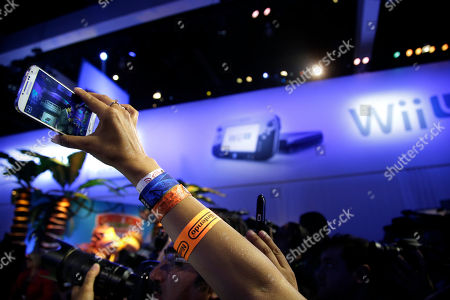 A show attendee uses her smartphone to record the remarks from Reggie Fils-Aime, President and chief operating officer of Nintendo of America, at the Nintendo Wii U software showcase during the E3 game show in Los Angeles