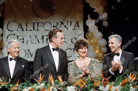 President George H. Bush receives a round of applause from California Governor George Deukmejian and his wife, Gloria, as Bush was introduced before the California Chamber of Commerce centennial dinner in Los Angeles on . Bush told business leaders they should put their free enterprise talents to work in Eastern Europe and Panama