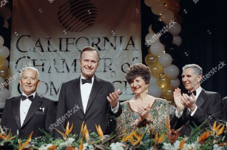 Stock Photo of President George H. Bush receives a round of applause from California Governor George Deukmejian and his wife, Gloria, as Bush was introduced before the California Chamber of Commerce centennial dinner in Los Angeles on . Bush told business leaders they should put their free enterprise talents to work in Eastern Europe and Panama. Man at left is unidentified
