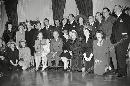 Harry Truman Film stars, who are taking part in Roosevelt birthday ball activities, pose in east room of White House, Washington, D.C., with President Harry S. Truman and members of his family. Front, left to right: Ilene Woods, Diana Lynn, Margaret Truman, Margaret O?Brien, President Truman, Mrs. Truman, Constance Moore, Dorothy Kilgallen, Eileen Barton. Back, L to R.: Jo Stafford, Lambert, Angela Lansbury, Helen Sioussat, Bracken, Paul Henreid, Zachary Scott, Alexis Cesar Romero, Lucy Munroe, William Bendix, Tecinald Gardiner, Sgt. Harvey stone and Charles Coburn. Stars were entertained at White House for luncheon