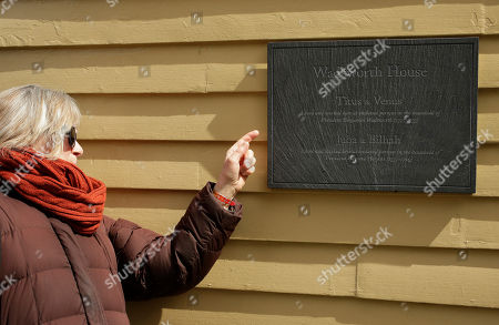 Stock Photo of Melissa Smith, of Cambridge, Mass., a Harvard Law School administrator, examines a newly unveiled plaque, at Harvard's Wadsworth House, on the school's campus, in Cambridge, Mass. The plaque honors four slaves that had been owned by and worked for Harvard's past presidents