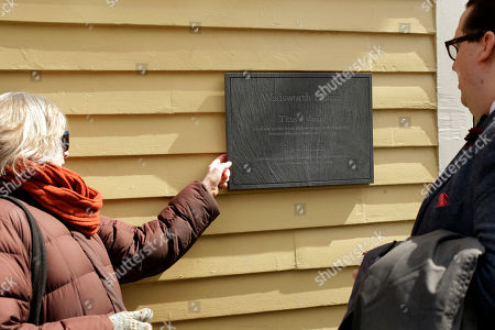 Melissa Smith, of Cambridge, Mass., left, a Harvard Law School administrator, and Kyle Courtney, of Hanover, Mass., right, a copyright advisor at Harvard, examine a newly unveiled plaque, at Harvard's Wadsworth House, on the school's campus, in Cambridge, Mass. The plaque honors four slaves that had been owned by and worked for Harvard's past presidents