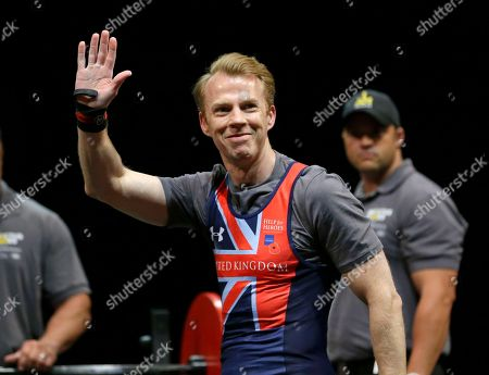 Stock Photo of Martin Cooper, of United Kingdom, waves to fans after completing a lift in the mens lightweight powerlifting competition at the Invictus Games, in Kissimmee, Fla