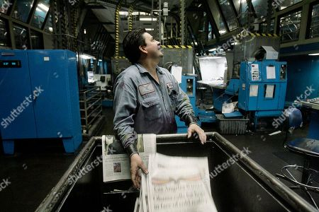 Press operator Al Calderon, at the Los Angeles Times pressroom facility, discards flawed copies of the paper, in Los Angeles. The Los Angeles Times has had to print additional papers because of demand associated with President Barack Obama taking office