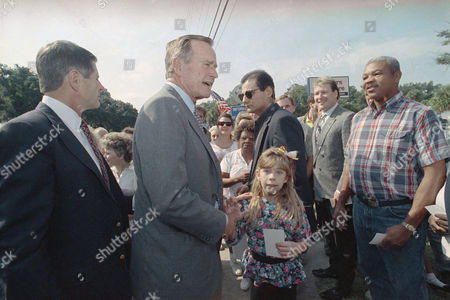 U.S. President George H. Bush greets Holly Campbell, 8, center, and others during a roadside stop, in Brunswick, Ga. Bush was en route to Sea Island, Ga., from the Brunswick airport when he stopped his motorcade to make the roadside visit