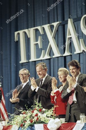 Robert Mitchum master of ceremonies, far left, U.S. President George H. Bush, left, Catherine Mosbacher, right, and Rick Perry, Agricultural Commissioner of Texas applaud during the Victory 92 dinner at night, in Houston