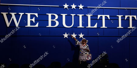 Michigan delegate Linda Lee Tarver poses with a sign inside the convention hall before the start of the Republican National Convention in Tampa, Fla., on
