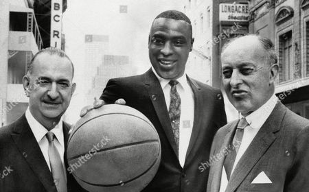 Cazzie Russell, of the University of Michigan and 1965 College Player of the Year, stands between Irving Mitchell Felt, left, board chairman of Madison Square Garden, and Ned Irish, Garden president, and holds a basketball after agreeing to terms with the New York Knickerbockers, . Russell reportedly agreed to a $200,000 long term contract