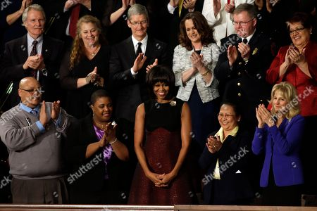 First lady Michelle Obama is applauded before President Barack Obama's State of the Union address during a joint session of Congress on Capitol Hill in Washington, . Front row, from left are, Nathaniel Pendleton, Cleopatra Cowley-Pendleton, Mrs. Obama, Menchu Sanchez and Jill Biden. Second row, from left are, Oregon Gov. John Kitzhaber, Deb Carey, Apple CEO Tim Cook, Amanda McMillan, Lt. Brian Murphy and Marie Lopez Rogers