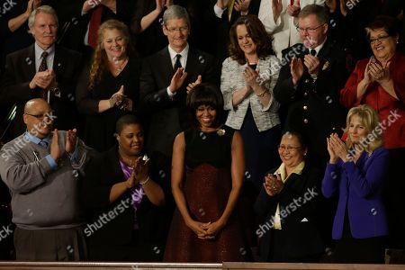 First lady Michelle Obama is applauded before President Barack Obama's State of the Union address during a joint session of Congress on Capitol Hill in Washington, . Front row, from left are, Nathaniel Pendleton, Cleopatra Cowley-Pendleton, Mrs. Obama, Menchu Sanchez and Jill Biden. Second row, from left are, Oregon Gov. John Kitzhaber, Deb Carey, Apple CDO Tim Cook, Amanda McMillan, Lt. Brian Murphy and Marie Lopez Rogers