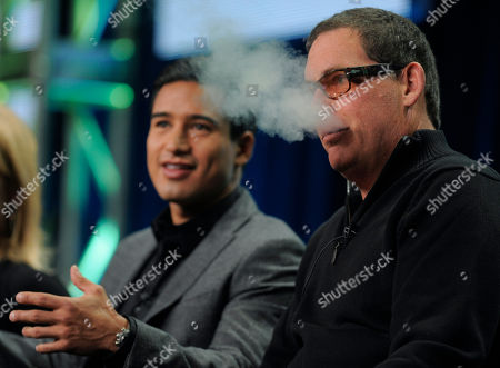 """Mike Fleiss, Mario Lopez Mike Fleiss, right, executive producer of the CW reality television series """"H8R,"""" blows smoke from an electric cigarette as he takes part in a panel discussion with the show's host/executive producer Mario Lopez at the CW Showtime summer press tour in Beverly Hills, Calif"""