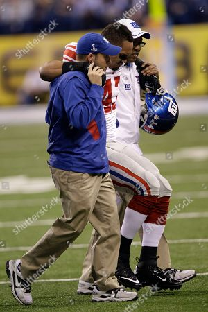 New York Giants tight end Travis Beckum is helped off the field after an injury during the first half of the NFL Super Bowl XLVI football game against the New England Patriots, in Indianapolis