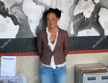 """Rachel Dolezal, a leader of the Human Rights Education Institute, stands in front of a mural she painted at the institute's offices in Coeur d'Alene, Idaho. Dolezal, the former NAACP chapter president who made headlines in June when her race came into question, faces that question, when she appears on the talk show """"The Real"""