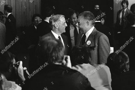 Walter Mondale, left, and Detroit Mayor Coleman Young, right, share a humorous moment after a rally for the former vice president at Metro Airport, Romulus, Mich. Mondale is gearing up for the Michigan caucuses this Saturday