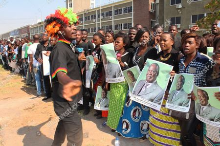 "Zambians sing and dance while waiting for the arrival of the body of former Zambian President Michael Sata to arrive at Kenneth Kaunda International Airport in Lusaka, Saturday, Nov,1, 2014. Zambian President Sata dubbed ""King Cobra"" for his sharp tongued remarks died in a London hospital Tuesday after a long illness"