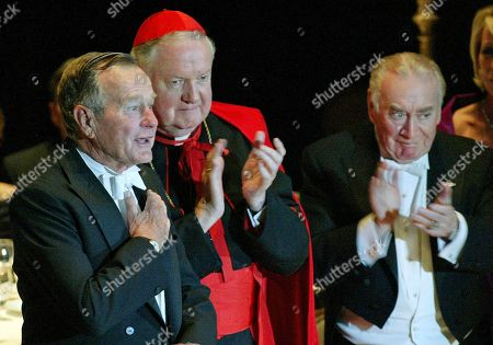 Stock Picture of CAREY, BUSH, EGAN Former President George H.W. Bush, left, is applauded by Archbishop of New York Cardinal Edward Egan and former Governor of the State of New York Hugh L. Carey, right, after Bush spoke at the 59th annual Alfred E. Smith Memorial Foundation Dinner at the Waldorf Astoria hotel in New York