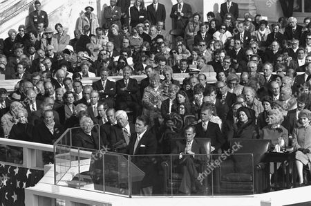 President Reagan delivers his inaugural address after being sworn in at the Capitol, . From right, are: Reagan's wife Nancy; Barbara Bush, wife of Vice President George Bush. Bush sits at center with his legs crossed; Sen. Mark Hatfield, R-OR, is behind Bush. Visible over the microphones are House Speaker Thomas P. O'Neill, D-MA, first row, and Rep. John Rhodes, R-AZ, second row