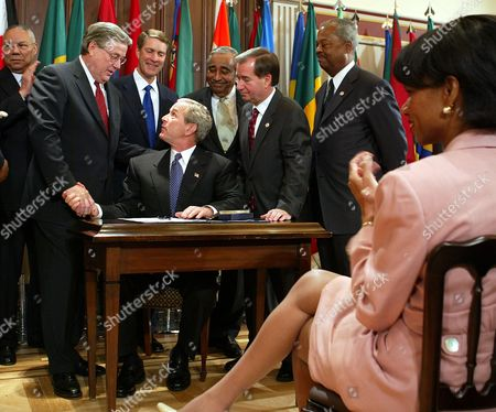 THOMAS President Bush shakes hands, with Rep. William Thomas, R-Calif., left, as National Security Adviser Condoleezza Rice, right, looks on. Bush had just signed the AGOA Acceleration Act of 2004 in Washington. Seen in back row, from the left; Secretary of State Colin Powell, Senate Majority Leader Sen. Bill Frist, R-Tenn., Rep. Charles Rangel, D-NY, Rep. Edward Royce, R-Calif.,Rep. Donald Payne, D-NJ