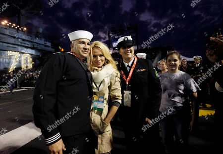 Stock Photo of Pamela Anderson Actress Pamela Anderson, center, poses for a picture with Navy sailors Samuel Bonilla, left, and Lisa Dubinski as North Carolina plays Michigan State in the first half of the Carrier Classic NCAA college basketball game aboard the USS Carl Vinson, in Coronado, Calif