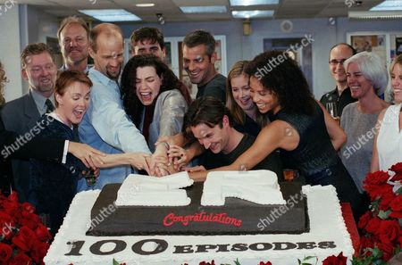 """ER"""" cast members, left to right: Laura Innes, Anthony Edwards, Julianna Margulies, George Clooney, Noah Wyle, Kellie Martin, and Gloria Ruben, cut a cake celebrating the 100th episode of the hit NBC television series on the set at Warner Brothers Studios in Los Angeles, . Also pictured in the second row from left to right are NBC President Warren Littlefield and series creator John Wells. The man behind Margulies is unidentified"""