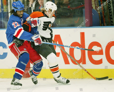 Stock Image of CARTER ROENICK New York Rangers' Anson Carter, left, and Philadelphia Flyers' Jeremy Roenick scramble for control of the puck in the first period of their game, at Madison Square Garden in New York