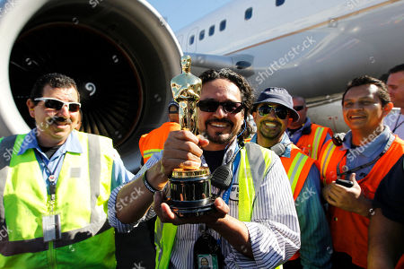 Tom Sherak United Airlines baggage handlers posing with a Oscar statue at Los Angeles International Airport in Los Angeles, . The awards will be distributed at the 84th annual Academy Awards on Feb. 26 at the Kodak Theatre in the Hollywood section of Los Angeles