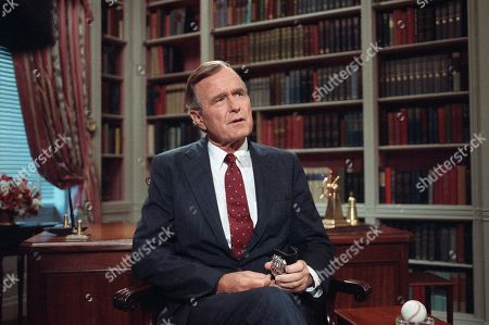 """U.S. President George H. Bush appears in the White House library after he delivered a televised address to the nation's schoolchildren, in Washington. The president told the children that """"saying no to drug's won't make you a nerd."""" The president is holding a badge that belonged to New York City police officer Eddie Byrne who was killed in 1988 while protecting a witness in a drug case"""