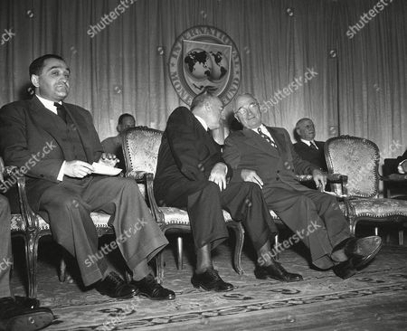 Stock Image of President Harry Truman, waiting to address the fourth annual conference of the World Bank and International Monetary Fund governors in Washington,, stretches his legs in comfort on the stagewhile talking with Secretary of the Treasury John Snyder. Snyder represents the United States as Governor for both the World Bank and the International Monetary Fund