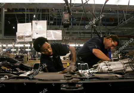 Arkivfoto av Leslie Murphy, left, and Steve Moulton, both from Toledo, work on a drive shaft on an assembly line at Daimler Chrysler's, Jeep plant in Toledo, Ohio