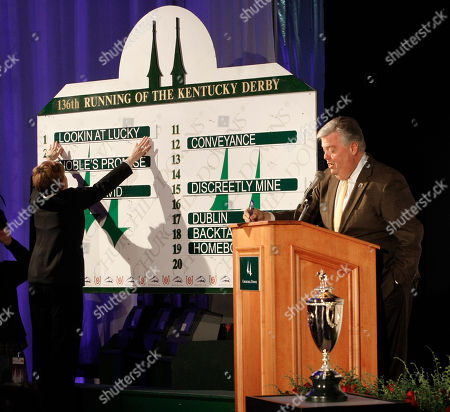 Stock Photo of John Asher, Julianna Oxley The Kentucky Derby winner's trophy sits at bottom right as Churchill Downs vice president for racing communications John Asher announces the number one post position for the race's morning line favorite Lookin at Lucky during the post position draw for the Kentucky Derby, in Louisville, Ky. Julianna Oxley hangs the name on the board