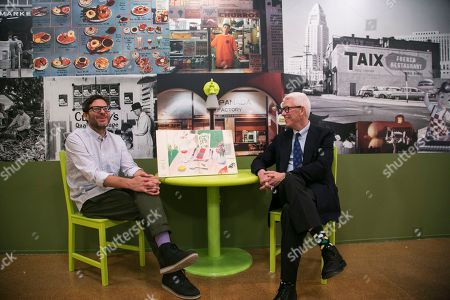 """Josh Kun, Ken Brecher Josh Kun, editor and curator, left, and Library Foundation of Los Angeles President, Ken Brecher, sit next to a 1970's vintage menu cover for Ma Maison restaurant designed by artist David Hockney, included in the exhibit, """"To Live and Dine in L.A."""" at the Los Angeles Public Library, in Los Angeles. Two LAPL librarians began collecting menus in the 1980s. Today the library is in possession of about 15,000 menus, the oldest dating back to 1875"""