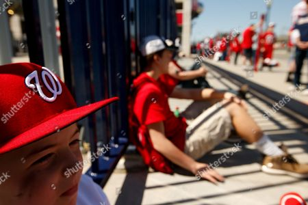 Jack Lewis, 12, of Arlington, Va., left, waits for the stadium to open at the center field gate before a baseball game between the Washington Nationals and the New York Mets on opening day at at Nationals Park, in Washington