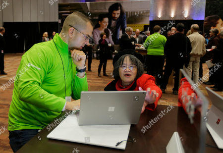 Brad Davis Brad Davis, left, demonstrates a Microsoft Surface Book to a guest, at Microsoft's annual shareholders meeting in Bellevue, Wash
