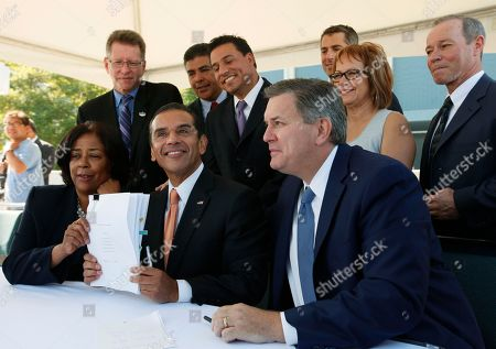"""Jan Perry, Antonio Villaraigosa, Tim Leiweke, Michael Linton, Tony Cardenas, Jose Huizar, Casey Wasserman, Maria Elena Durazo, Robbie Hunter Sitting from left: Councilwoman Jan Perry, Los Angeles Mayor Antonio Villaraigosa, and Anschutz Entertainment Group (AEG) President Tim Leiweke show the signed """"implementation agreement"""" for the modernization of the Los Angeles Convention Center and the construction of a new NFL stadium in downtown Los Angeles . Standing from left: Michael Linton Chief Marketing Officer at The Farmers Group, Inc., Councilman Tony Cardenas, Councilman Jose Huizar, Casey Wasserman, Chairman & CEO at Wasserman Media Group, Maria Elena Durazo, Executive Secretary and Treasurer Los Angeles County Federation of Labor, AFL-CIO, and Robbie Hunter, President Iron Workers Union"""