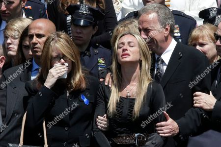 Police officer Brian Moore's mother Irene, left, sister Christine, center, and father Raymond react as his casket is placed in the hearse after his funeral mass, at the St. James Roman Catholic church in Seaford, N.Y. The 25-year-old died Monday, two days after he was shot in Queens