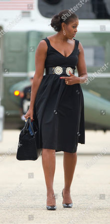 Michelle Obama First lady Michelle Obama walks across the tarmac before boarding Air Force One before her departure from Andrews Air Force Base, . The Obama family is traveling to Westchester County, NY., to attend the wedding ceremony of White House chef Sam Kass and MSNBC host Alex Wagner